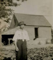 Norman Kent dressed in his best standing W. side of granary; circa 1910.